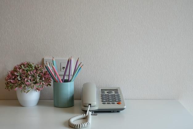 Telefon und blumentopf und pastellstifte im blauen glas auf dem schreibtisch auf grauem wandhintergrund