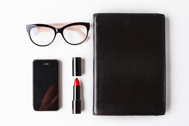 Telefon und notizbuch der roten lippenstiftbrille über weißem hintergrund