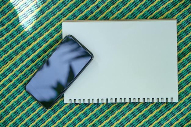 Telefon und smartphones. notizbuch, auf die matte grün kariert gelegt