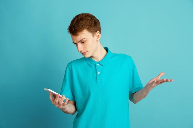 Telefon verwenden. das moderne porträt des kaukasischen jungen mannes lokalisiert auf blauer wand, monochrom. schönes männliches model. konzept der menschlichen emotionen, gesichtsausdruck, verkauf, anzeige, trendy.