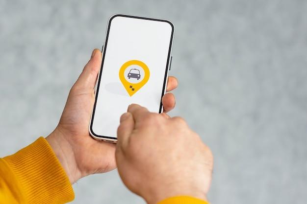 Telefondisplay mit taxi-symbol auf hellem hintergrund. mann hält ein mockup-smartphone in der handnahaufnahme.