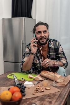 Telefongespräch. glücklicher gutaussehender mann, der einen stock mit käse hält, während er ein telefongespräch führt