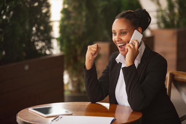Telefonieren, gewinner. afroamerikanische geschäftsfrau in bürokleidung lächelnd, sieht selbstbewusst glücklich, beschäftigt aus. konzept für finanzen, wirtschaft, gleichstellung und menschenrechte. schönes junges modell, erfolgreich.