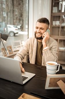 Telefonieren. strahlender lachender kerl, der sich mit geschäftsarbeit befasst, während er mit laptop und smartphone im schrank bleibt