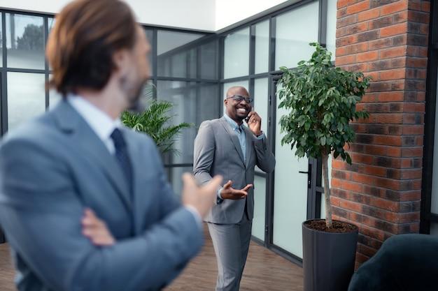 Telefonisch sprechen. dunkelhäutiger geschäftsmann, der beim telefonieren lächelt, der in der nähe eines kollegen steht