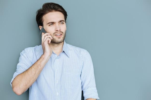 Telefonische kommunikation. schlauer netter, selbstbewusster mann, der steht und ein telefon an sein ohr legt, während er einen anruf tätigt