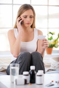 Telefonische rücksprache mit dem arzt. junge kranke frau, die telefoniert, während sie in ihrer wohnung im bett sitzt, mit medikamenten im vordergrund