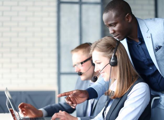 Telefonistin, die im callcenter-büro arbeitet und seinem kollegen hilft