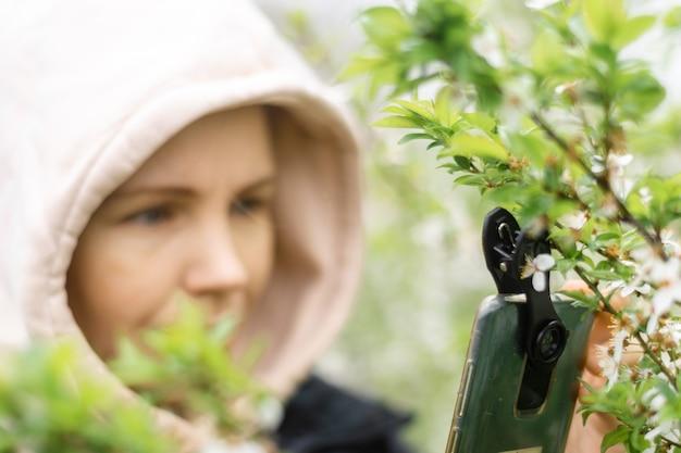 Telefonobjektive für die makrofotografie. eine frau hält ein handy mit makroaufsatz in der hand und fotografiert pflanzen.