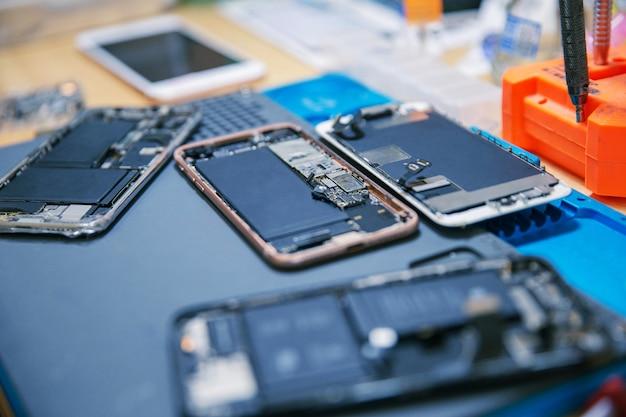 Telefonreparaturkonzept mehrere elektronische geräte, die in die komponenten wie abdeckungen, platinen, gehäuse zerlegt werden.