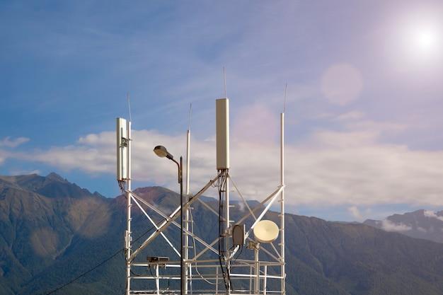 Telekommunikationssender 4g, 5g. mobilfunkbasisstation mit sendeantennen in der nähe der straße vor dem hintergrund der berge.