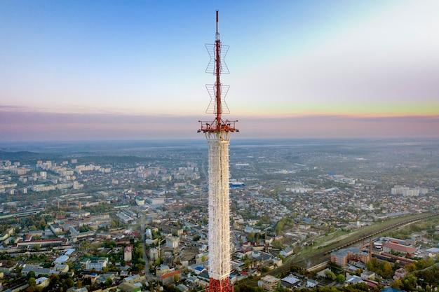 Telekommunikationsturm für mobiltelefondienst und drahtlose 5g-kommunikation. vor dem hintergrund der stadt