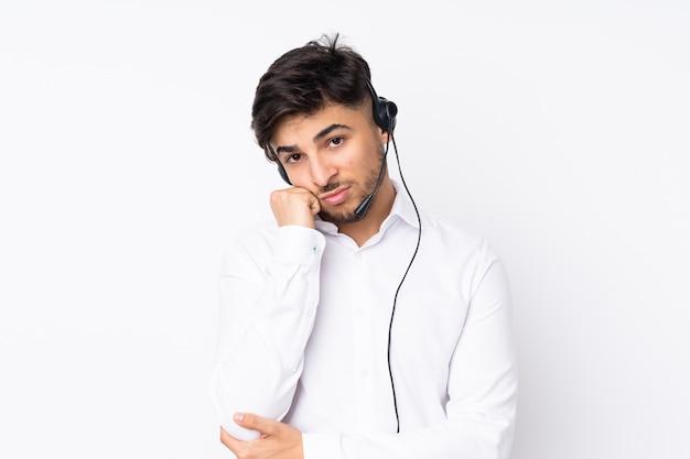 Telemarketer arbeiten mit einem headset isoliert auf weißer wand unglücklich und frustriert