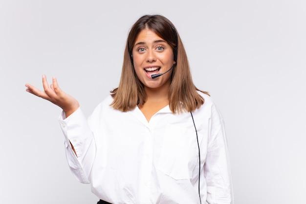 Telemarketer der jungen frau, die glücklich, überrascht und fröhlich fühlt und mit positiver einstellung lächelt
