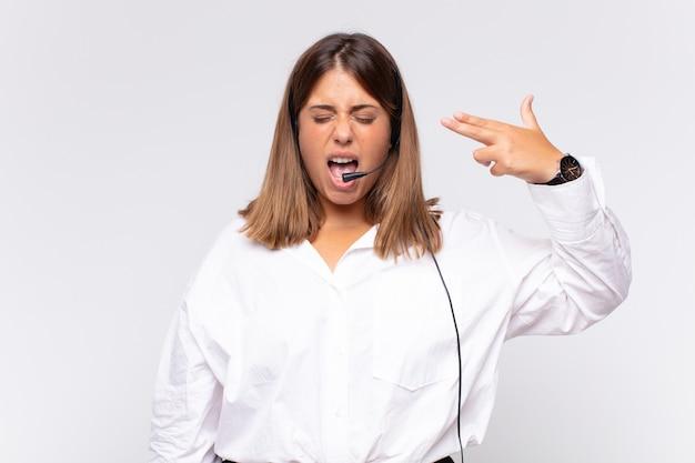 Telemarketer der jungen frau, die unglücklich und gestresst schaut, selbstmordgeste, die waffenzeichen mit der hand macht, zeigt auf kopf