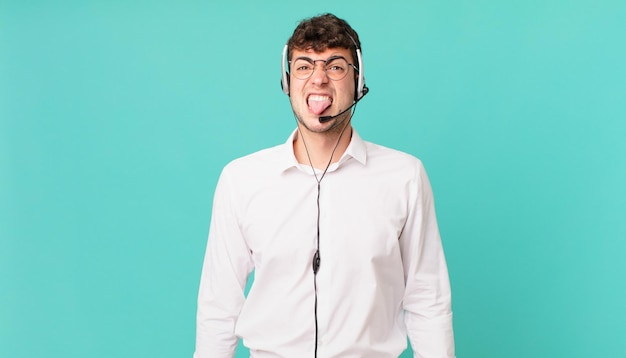 Telemarketer, der sich angewidert und irritiert fühlt, die zunge herausstreckt, etwas böses und ekelhaftes nicht mag