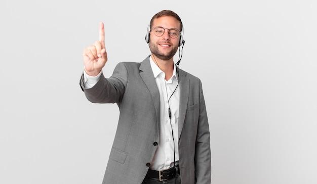 Telemarketer geschäftsmann lächelt und sieht freundlich aus und zeigt nummer eins