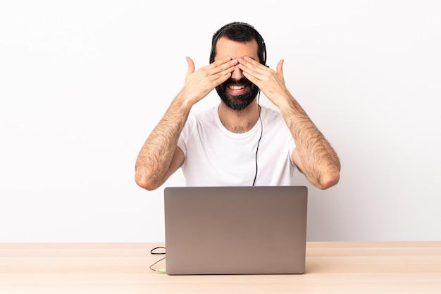 Telemarketer kaukasischer mann, der mit einem headset und mit laptop arbeitet, der augen durch hände und lächeln kegelt.