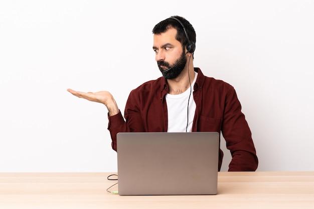 Telemarketer kaukasischer mann, der mit einem headset und mit laptop arbeitet, der copyspace mit zweifeln hält.
