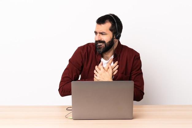 Telemarketer kaukasischer mann, der mit einem headset und mit laptop arbeitet, der einen schmerz im herzen hat.