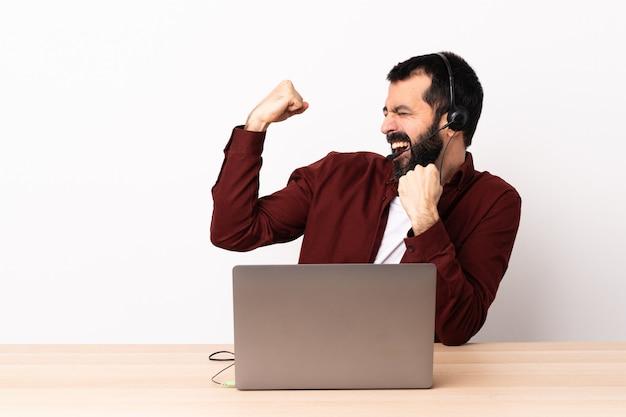 Telemarketer kaukasischer mann, der mit einem headset und mit laptop arbeitet, der einen sieg feiert.