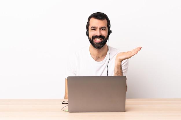 Telemarketer kaukasischer mann, der mit einem headset und mit laptop arbeitet, der imaginären copyspace auf der handfläche hält, um eine anzeige einzufügen.