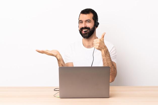 Telemarketer kaukasischer mann, der mit einem headset und mit laptop arbeitet, der imaginären copyspace auf der handfläche hält, um eine anzeige und mit daumen hoch einzufügen.