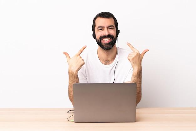 Telemarketer kaukasischer mann, der mit einem headset und mit laptop arbeitet und eine daumen hoch geste gibt.