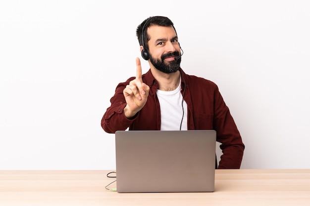 Telemarketer kaukasischer mann, der mit einem headset und mit laptop arbeitet und einen finger zeigt.