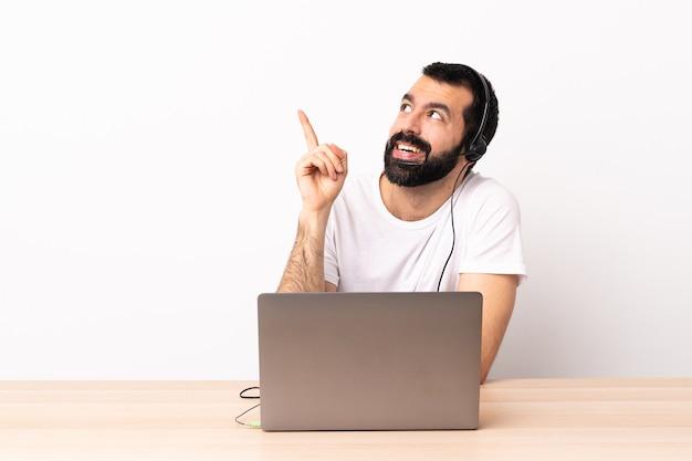 Telemarketer kaukasischer mann, der mit einem headset und mit laptop arbeitet, zeigt eine große idee auf.