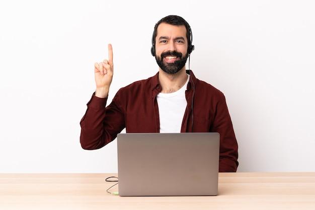 Telemarketer kaukasischer mann, der mit einem headset und mit laptop arbeitet, zeigt eine große idee auf