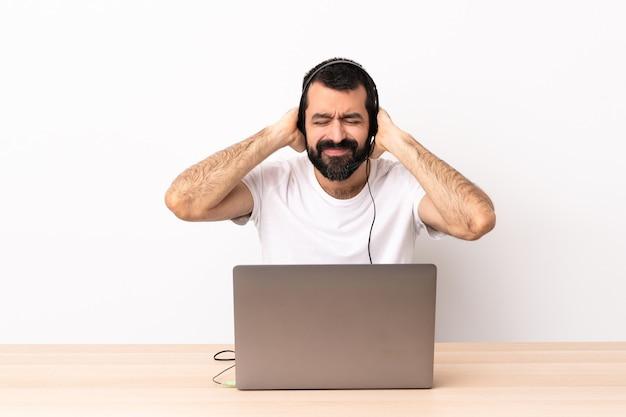 Telemarketer kaukasischer mann, der mit einem headset und mit laptop frustriert arbeitet und ohren bedeckt.
