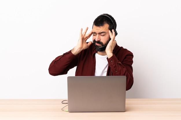 Telemarketer kaukasischer mann, der mit einem headset und mit laptop mit kopfschmerzen arbeitet