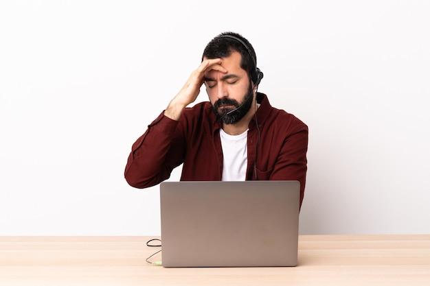 Telemarketer kaukasischer mann, der mit einem headset und mit laptop mit kopfschmerzen arbeitet.