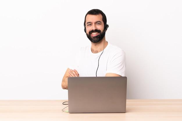 Telemarketer kaukasischer mann, der mit einem headset und mit laptop mit verschränkten armen arbeitet und nach vorne schaut.