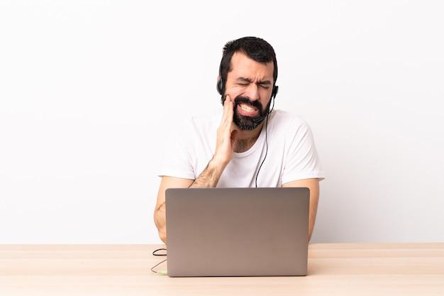 Telemarketer kaukasischer mann, der mit einem headset und mit laptop mit zahnschmerzen arbeitet.