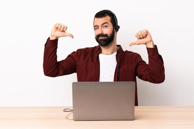 Telemarketer kaukasischer mann, der mit einem headset und mit laptop stolz und selbstzufrieden arbeitet.