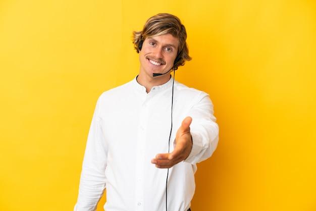 Telemarketer-mann, der mit einem auf gelber wand isolierten headset arbeitet, das hände schüttelt, um ein gutes geschäft zu schließen
