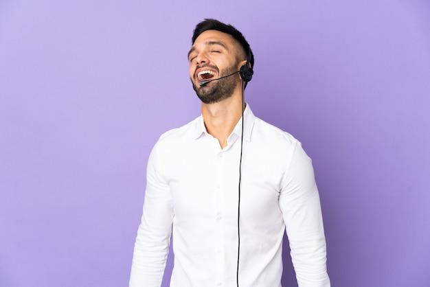 Telemarketer-mann, der mit einem auf lila hintergrund isolierten headset arbeitet, lacht