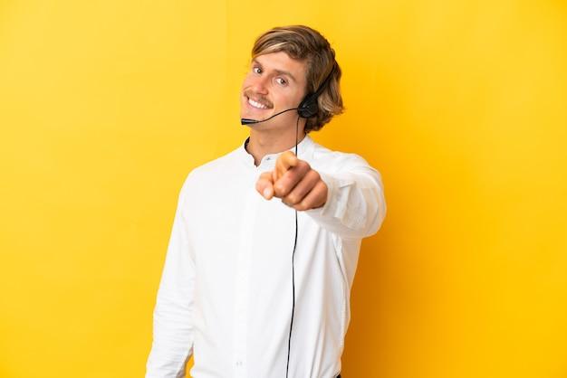Telemarketer-mann, der mit einem headset arbeitet, das auf gelbe wand lokalisiert zeigt, zeigt front mit glücklichem ausdruck