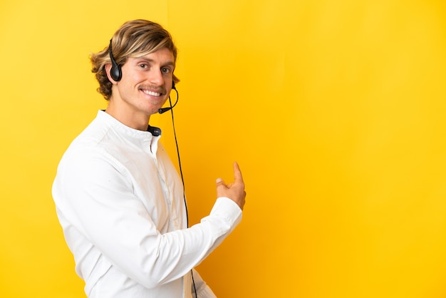 Telemarketer-mann, der mit einem headset arbeitet, das auf gelbe wand lokalisiert zurück zeigt