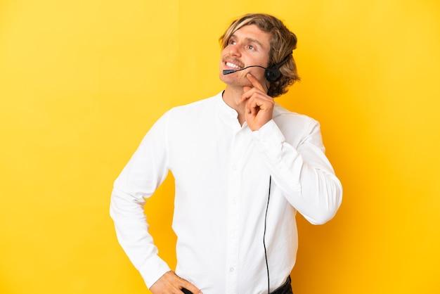 Telemarketer-mann, der mit einem headset arbeitet, das auf gelbem lokalisiertem denken einer idee beim aufblicken isoliert wird