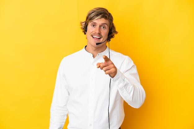 Telemarketer-mann, der mit einem headset arbeitet, das auf gelber wand isoliert ist, überrascht und nach vorne zeigend