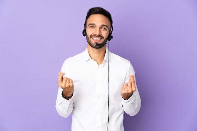 Telemarketer-mann, der mit einem headset arbeitet, das auf lila hintergrund lokalisiert wird, der geldgeste macht