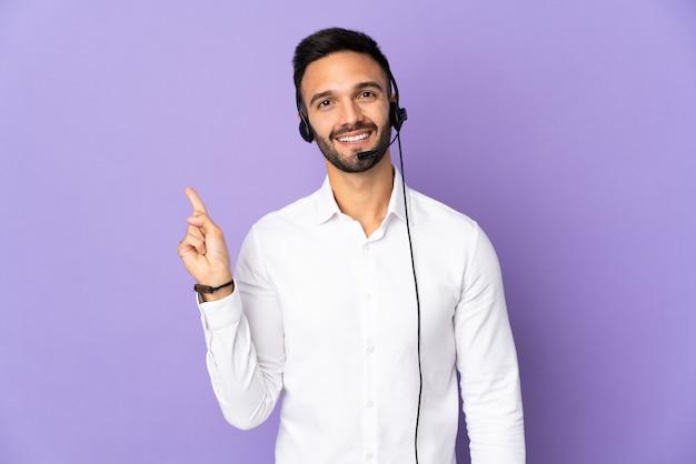 Telemarketer-mann, der mit einem headset arbeitet, das auf lila wand lokalisiert wird, die einen finger im zeichen des besten zeigt und hebt