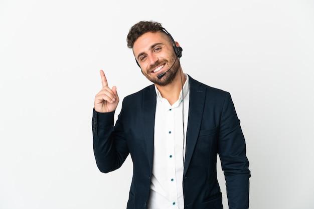 Telemarketer-mann, der mit einem headset arbeitet, das auf weißem hintergrund isoliert ist und einen finger im zeichen des besten zeigt und hebt