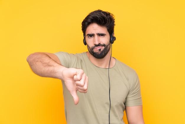 Telemarketer-mann, der mit einem headset über isolierter gelber wand arbeitet, die daumen-unten-zeichen zeigt