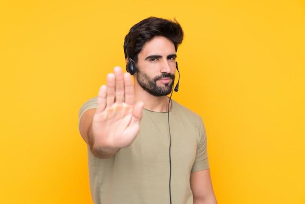 Telemarketer-mann, der mit einem headset über isolierter gelber wand arbeitet, die stopp-geste mit ihrer hand macht