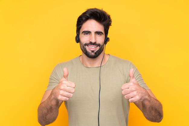 Telemarketer-mann, der mit einem headset über isolierter gelber wand arbeitet und eine daumen hoch geste gibt