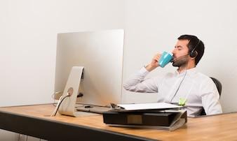 Telemarketer-Mann in einem Büro, das einen Tasse Kaffee hält